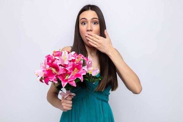 Bang bedekte mond met hand mooi jong meisje op gelukkige vrouwendag met boeket geïsoleerd op een witte muur