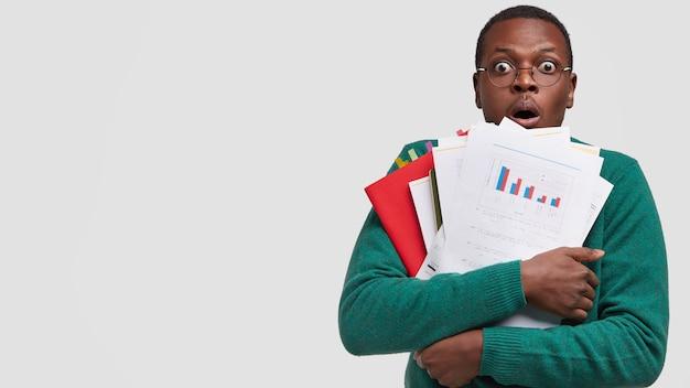 Bang bedrijfseigenaar draagt veel documenten, organisator, staart met afgeluisterde ogen, opent mond