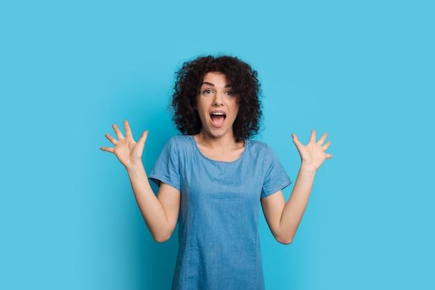 Bang blanke vrouw met krullend haar gebaart angst op een blauwe muur tijdens het openen van mond