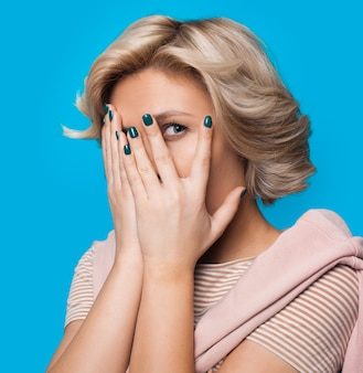 Bang blonde dame die haar gezicht bedekt met palmen die camera op een blauwe studiomuur bekijken
