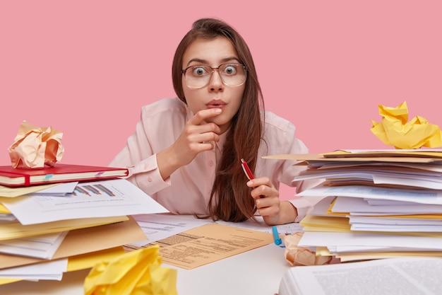 Bang brunette mooi schoolmeisje zit op bureau thuis, stapel papieren rond, pen houdt, vierkante bril draagt, gezichtsuitdrukking heeft verbaasd