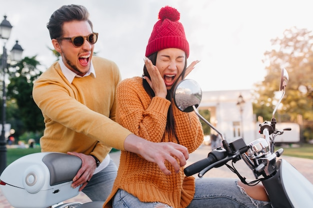 Bang dame in gebreide muts zittend op scooter met ogen dicht