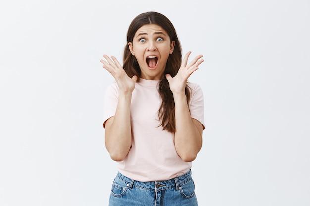 Bang en geschokt jonge brunette poseren