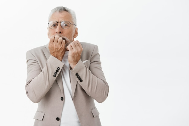 Bang en geschokt senior man vingernagels bijten en angstig op zoek