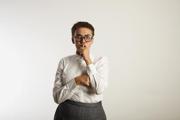 Bang en moe uitziende leraar in diepe gedachte op witte muur