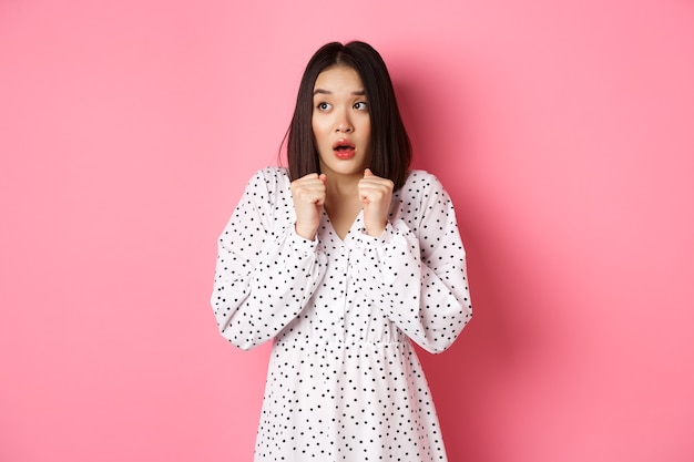 Bang en timide aziatisch meisje, bevend van angst, starend naar links en hijgend in jurk over roze...