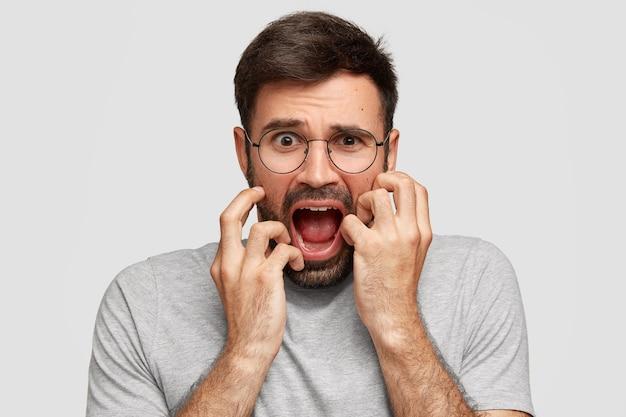 Bang geërgerd mannetje opent mond en fronst zijn wenkbrauwen, houdt de handen op de wangen, kijkt wanhopig, is in paniek, draagt losse grijze kleding, staat alleen tegen een witte muur. negatieve gevoelens