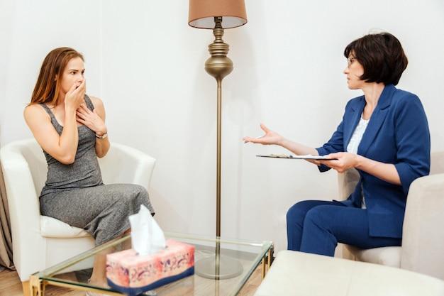 Bang gemaakt meisje kijkt naar arts. ze is doodsbang. vrouw bedekt mond met handen. arts zit voor vrouw nad praten met haar. ze houdt tablet voor papieren.