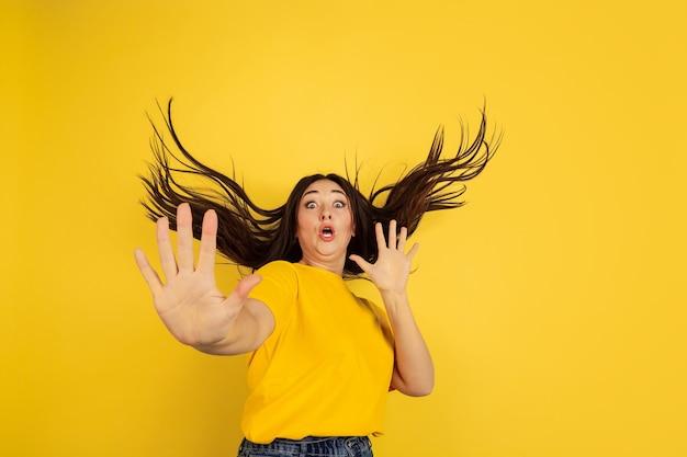 Bang, geschokt. blanke vrouw portret geïsoleerd op gele muur. mooi vrouwelijk donkerbruin model in informele stijl. concept van menselijke emoties, gezichtsuitdrukking, verkoop, copyspace.