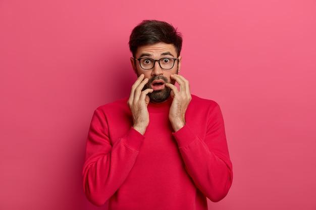 Bang geschokt man staart, heeft fobie, voelt zich doodsbang, heeft een gealarmeerde gezichtsuitdrukking, draagt een bril, grijpt het gezicht, geïsoleerd op een roze muur. bange man hoort wild nieuws