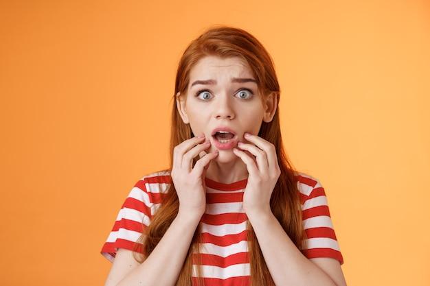 Bang geschokt roodharige vrouw maakt zich zorgen, staar camera sprakeloos naar adem happend bezorgd, aanraking lippen laten vallen kaak verbaasd, hoor angstaanjagend eng nieuws, sta verdoofd op oranje achtergrond, erg overstuur