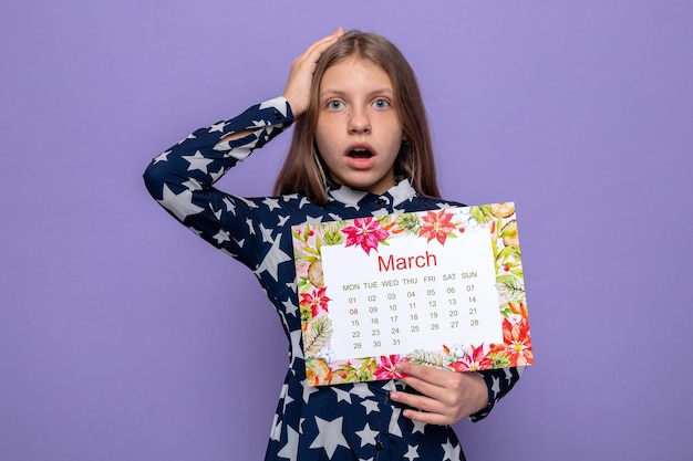 Bang greep het hoofd van een mooi klein meisje op de dag van een gelukkige vrouw met een kalender geïsoleerd op een blauwe muur