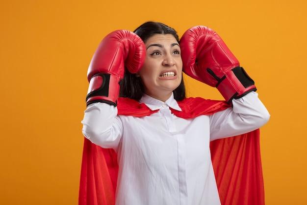 Bang jong kaukasisch superheromeisje die dooshandschoenen dragen die handen op hoofd houden die rechtuit kijken geïsoleerd op oranje achtergrond met exemplaarruimte