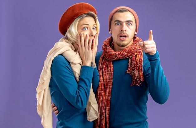 Bang jong koppel met hoed met sjaal op valentijnsdag meisje bedekt mond met hand man wijst naar camera geïsoleerd op blauwe achtergrond