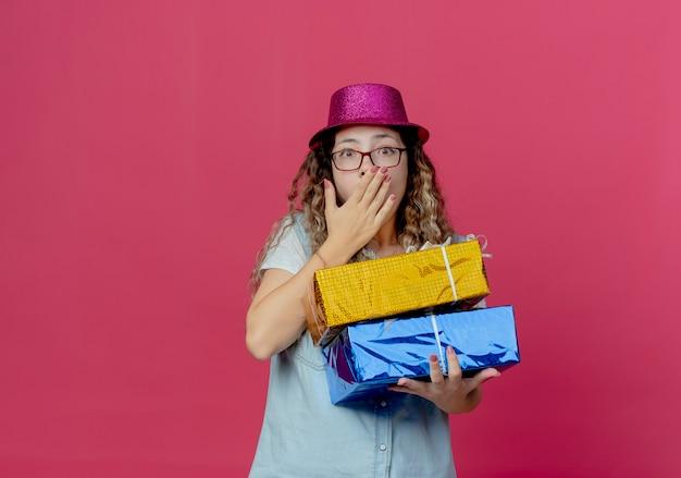 Bang jong meisje met bril en roze hoed met geschenkdozen en bedekte mond met hand geïsoleerd op roze