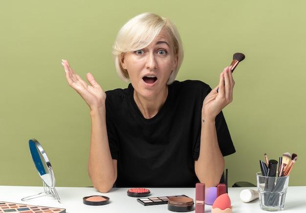 Bang jong mooi meisje zit aan tafel met make-uptools met poederborstel geïsoleerd op olijfgroene achtergrond