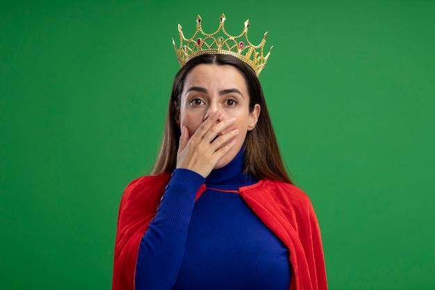 Bang jong superheromeisje die kroon overdekte mond met hand dragen die op groen wordt geïsoleerd