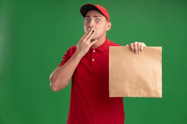 Bang jonge bezorger met uniform en pet met papier voedselpakket bedekte mond met hand geïsoleerd op groene muur