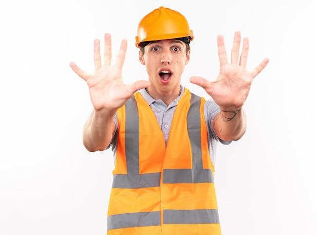 Bang jonge bouwer man in uniform weergegeven: stop gebaar geïsoleerd op een witte muur