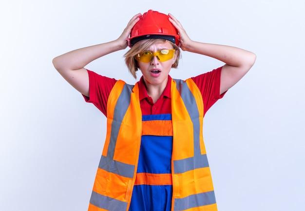 Bang jonge bouwer vrouw in uniform met bril pakte hoofd geïsoleerd op witte achtergrond