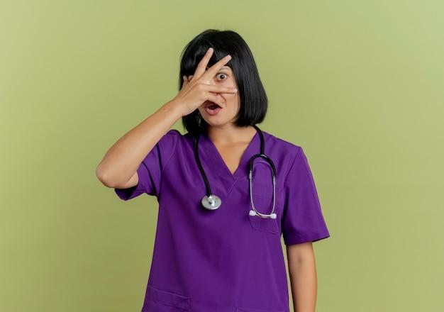 Bang jonge brunette vrouwelijke arts in uniform met stethoscoop legt hand op gezicht en kijkt door vingers geïsoleerd op olijfgroene achtergrond met kopie ruimte