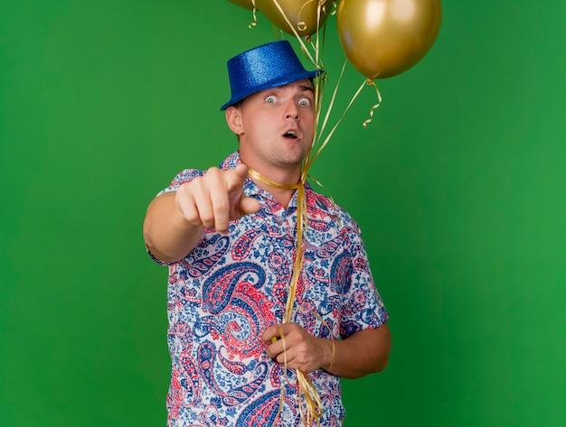 Bang jonge feestman met blauwe hoed met ballonnen om de nek gebonden en toont je gebaar geïsoleerd op groen