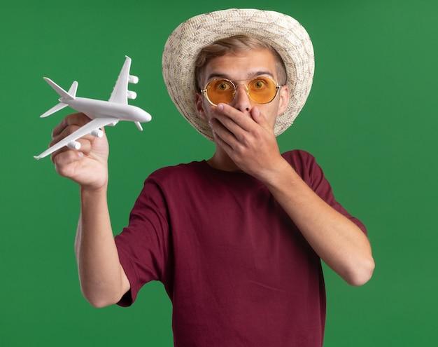 Bang jonge knappe kerel die rood shirt met bril en hoed draagt die speelgoedvliegtuig bedekte mond met hand houdt die op groene muur wordt geïsoleerd