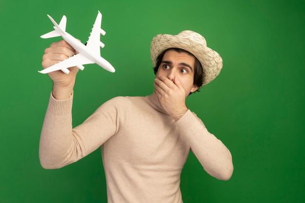 Bang jonge knappe kerel hoed dragen en verhogen en kijken naar speelgoed vliegtuig bedekte mond met hand geïsoleerd op groene muur