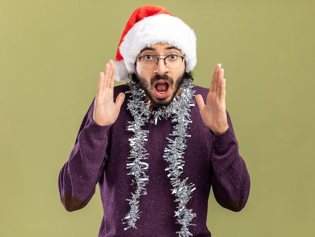 Bang jonge knappe kerel met kerstmuts met guirlande op nek hand in hand rond gezicht geïsoleerd op olijfgroene muur