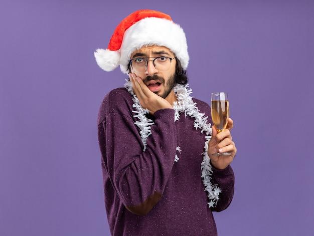 Bang jonge knappe kerel met kerstmuts met guirlande op nek met glas champagne hand op wang geïsoleerd op blauwe muur