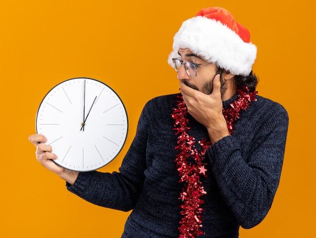 Bang jonge knappe kerel met kerstmuts met slinger op nek houden en kijken naar muur klok bedekt mond met hand geïsoleerd op een oranje achtergrond