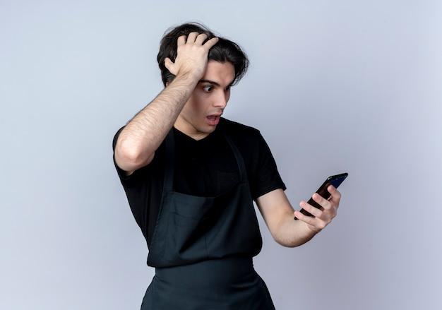 Bang jonge knappe mannelijke kapper in uniform bedrijf en telefoon kijken en greep hoofd geïsoleerd op wit
