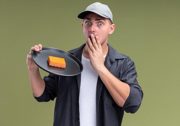 Bang jonge knappe schoonmaakster dragen t-shirt en pet houden spons op dienblad hand op wang zetten geïsoleerd op olijfgroene muur