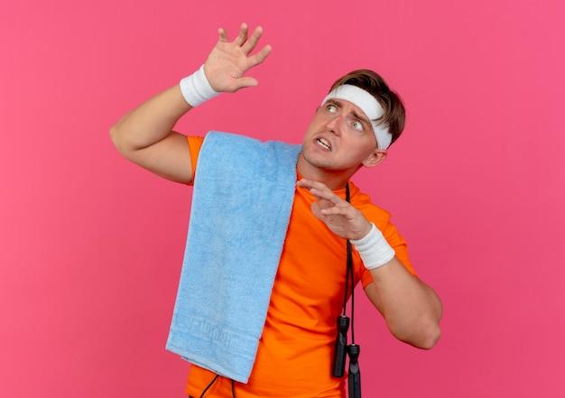 Bang jonge knappe sportieve man met hoofdband en polsbandjes met handdoek en springtouw om nek handen opheffen en opzoeken geïsoleerd op roze muur