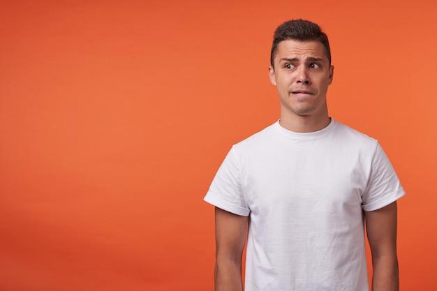 Bang jonge kortharige brunette man gekleed in vrijetijdskleding wrangly lippen bijten terwijl opzij kijken, handen langs het lichaam houden terwijl poseren op oranje achtergrond