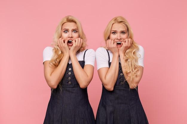Bang jonge lange witharige dames in elegante kleding die hun gezicht met opgeheven handen vasthouden terwijl ze bang naar de camera kijken, geïsoleerd op roze achtergrond
