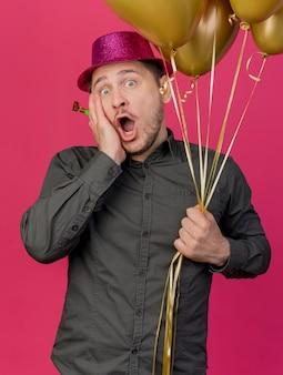 Bang jonge partij kerel die roze hoed draagt ?? die ballonnen met partijblazer houdt die hand op wang zetten die op roze wordt geïsoleerd