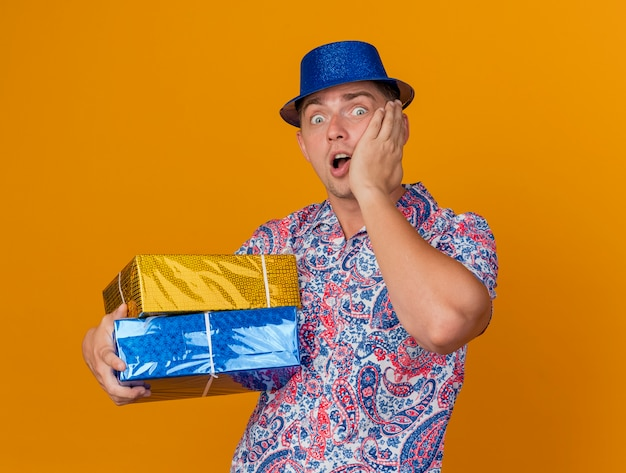 Bang jonge partij kerel dragen blauwe hoed houden geschenkdozen hand zetten wang geïsoleerd op oranje