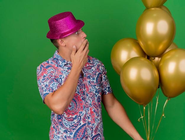 Bang jonge partij kerel dragen roze hoed houden en kijken naar ballonnen bedekt mond met hand geïsoleerd op groene achtergrond