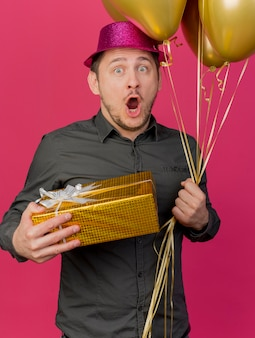Bang jonge partij kerel dragen roze hoed houden geschenkdoos met ballonnen geïsoleerd op roze achtergrond