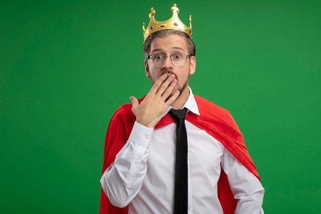 Bang jonge superheld kerel dragen kroon en stropdas bedekte mond met hand geïsoleerd op groene achtergrond