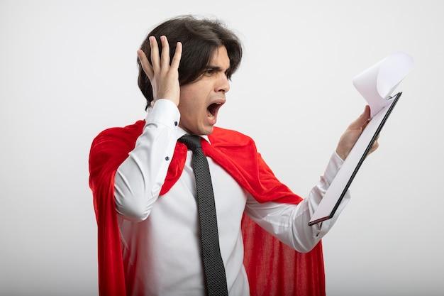 Bang jonge superheld kerel dragen stropdas houden en kijken naar klembord hand op hoofd zetten