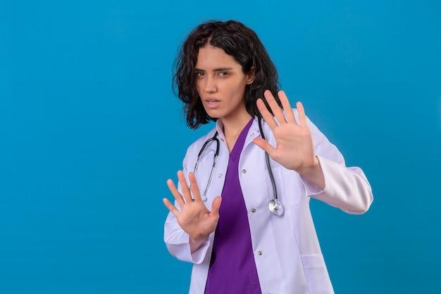 Bang jonge vrouw arts die witte jas draagt met een stethoscoop die haar handen omhoog houdt en vertelt kom niet dichterbij op geïsoleerd blauw