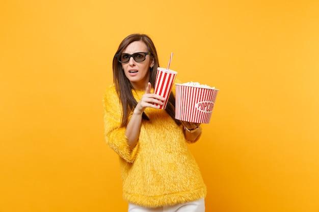 Bang jonge vrouw in 3d imax bril wijzende wijsvinger, kijken naar film film houden emmer popcorn kopje cola of frisdrank geïsoleerd op gele achtergrond. mensen oprechte emoties in de bioscoop, levensstijl.