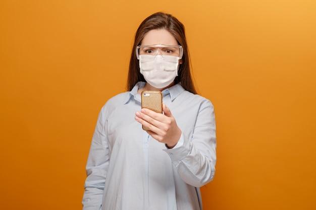 Bang jonge vrouw met een medisch masker op haar gezicht kijkt naar de telefoon, vrouw in paniek over epidemie