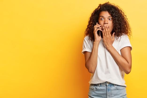 Bang jonge vrouw met krullend haar poseren met haar telefoon