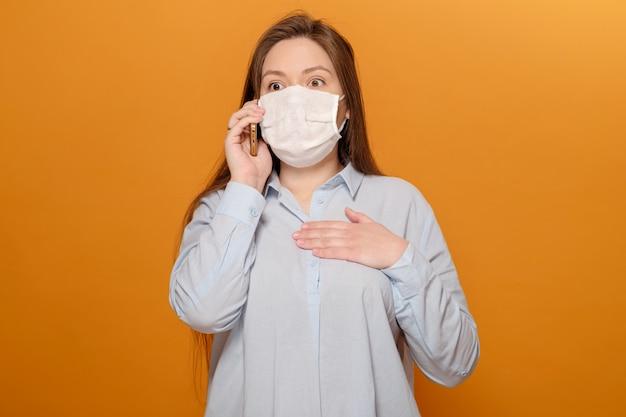 Bang jonge vrouw met medische masker op haar gezicht kijkt naar telefoon, vrouw in paniek over epidemie, praten aan de telefoon