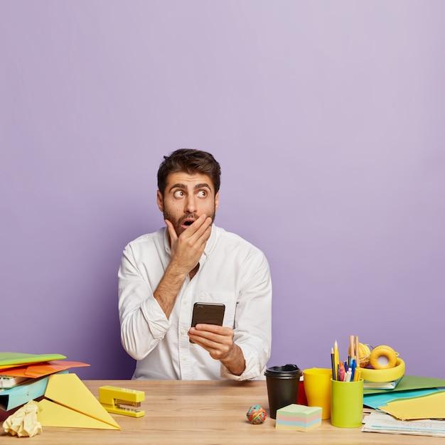 Bang jonge zakenman kijkt boven, houdt moderne smartphone, mond bedekt, houdt moderne mobiele telefoon in de hand, gekleed in een wit overhemd