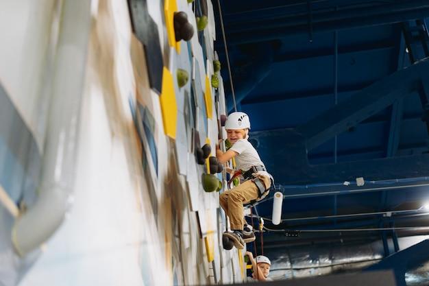 Bang jongetje klimt op de muur in avonturenpark langs hindernisbaan. hoog touwpark binnenshuis. hoge kwaliteit foto