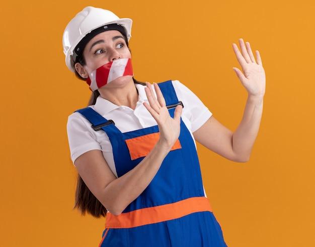 Bang kijken naar jonge bouwersvrouw aan de zijkant in uniform verzegelde mond met ducttape die stopgebaar toont dat op oranje muur wordt geïsoleerd